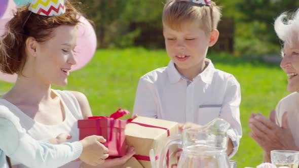 Thumbnail for Mother Receiving Birthday Gifts from Kids on Outdoor Family Party