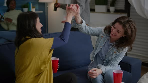 Cheerful Women Celebrating Friendship with High Five Late at Night