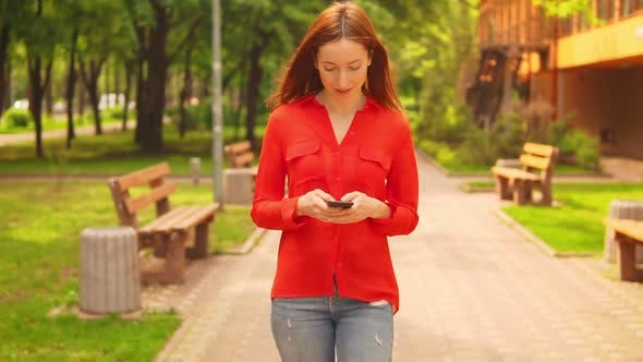 Thumbnail for a Redheaded Businesswoman Holding Mobile Walking