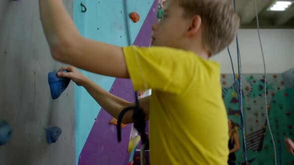 Thumbnail for Caucasian Teenager Climbing up Wall during Group Practice