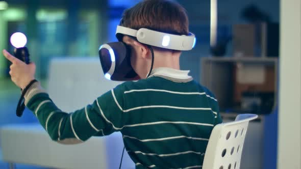 Thumbnail for Little Boy with Virtual Reality Motion Controllers Having Immersive Gaming Experience