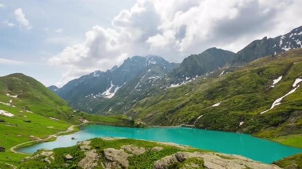 Thumbnail for Time lapse: mountain peaks and emerald green alpine lake with moving clouds on the italian Alps