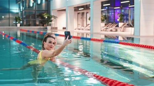 Young Females in the Swimming Pool Two Beautiful Females in the Yellow Swimsuits Take a Selfie on a