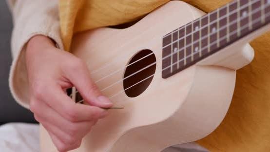 Thumbnail for Mädchen spielen Ukulele zu Hause