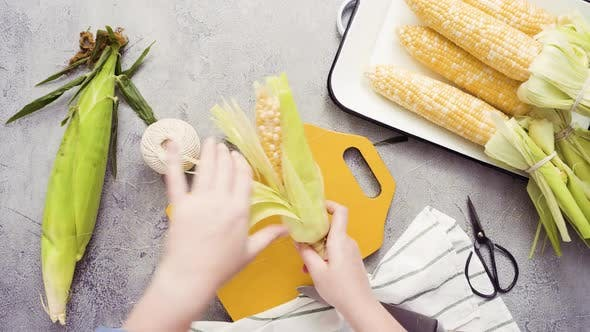 Thumbnail for Step by step. Shucking organic corn to make Mexican corn on the cob Elote.
