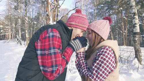 Beautiful Couple of Smiling Young People in a Snowy Forest on a Sunny Day Warming Their Hands with