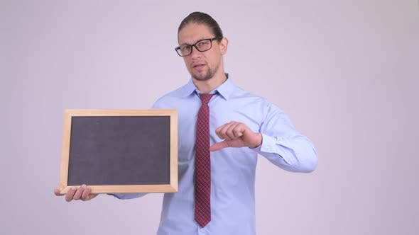 Thumbnail for Stressed Businessman Holding Blackboard and Giving Thumbs Down