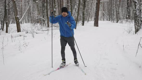 A Young Man Is Engaged in Crosscountry Skiing in the Winter Forest