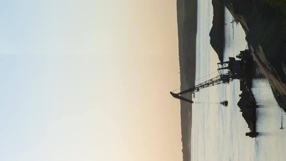 Barge Crane Silhouette Works Near Dark Sandy Bank of River