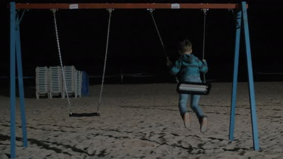 Cover Image for Kid Swinging Alone on the Beach at Night