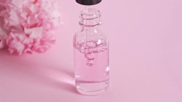 Bottle with a pipette gaining serum oil or perfume essence.