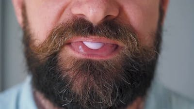 Bearded Man Chewing Bubble Gum. Man Blowing Out a Bubble of Chewing Gum