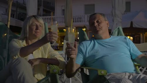 Senior adult man and woman drinking cocktails
