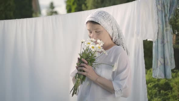 Thumbnail for Cute Mature Woman with White Shawl on Her Head Tears Off Daisy Petals at the Clothesline Outdoors