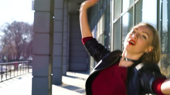 Blond Young Woman Dancing Contemporary Dance in Rays of Sunset in Urban Environment