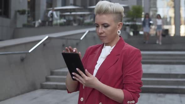 Successful girl with a tablet in hands near a business center