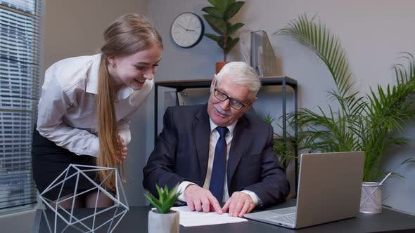 Senior Businessman Examining Financial Data with Woman Colleague Celebrating Good Financial Results