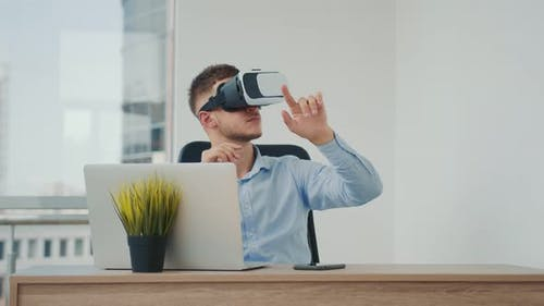 A Young Man Sitting at a Desk in the Office Uses Augmented Reality Glasses To Work on Business