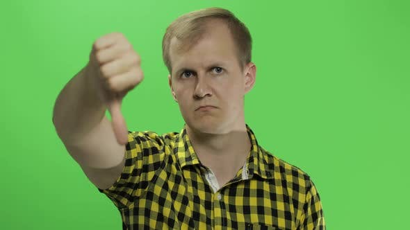 Thumbnail for Caucasian Young Man in Yellow Shirt Showing No and Giving His Thumb Down