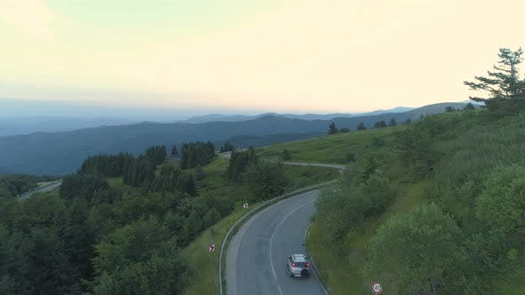 Aerial View Drone Tracking Silver SUV Driving Through Mountain Passage Road with Green Hills