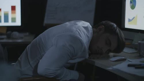Tired Business Man Sleeping on Desk Front Computer Screen in Night Office.