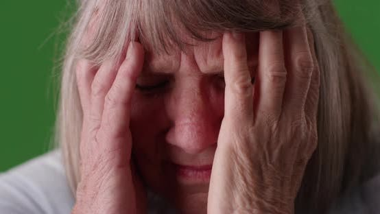 Thumbnail for Tight shot of elderly woman with migraine headache in front of greenscreen
