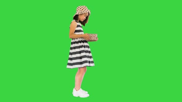 Thumbnail for Asian Girl Opening a Box with a Present on a Green Screen, Chroma Key.