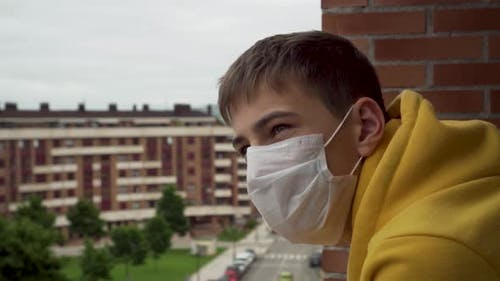 Young man in a medical protective mask sadly looks from the balcony during coronavirus quarantine.