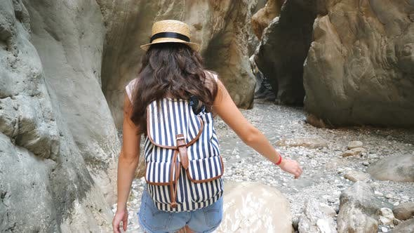 Thumbnail for Unrecognizable Young Woman with Backpack Walking Across Narrow Canyon. Hiker in Hat Strolling in