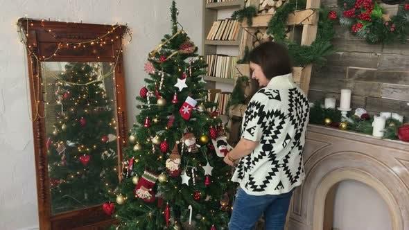 Frau schmückt Weihnachtsbaum von verschiedenen Spielzeugen