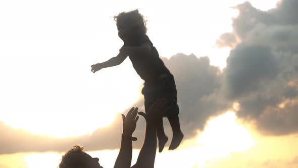 Thumbnail for Silhouette of a Father Playfully Throwing His Son in the Air