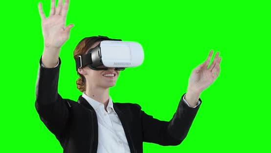 Caucasian woman wearing a VR headset on green background
