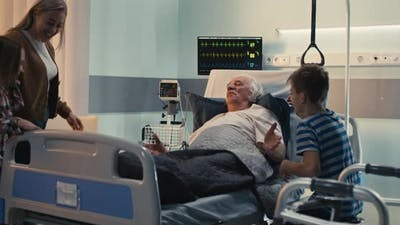 Happy Family Visiting Elderly Man in Hospital
