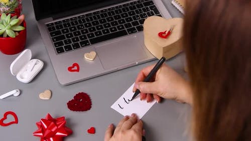 Young woman writing a card I LOVE YOU and wrapping valentine's day gift