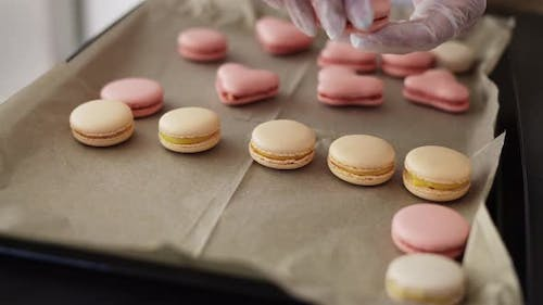 Female Hands Putting Filled Macaroons in a Tray