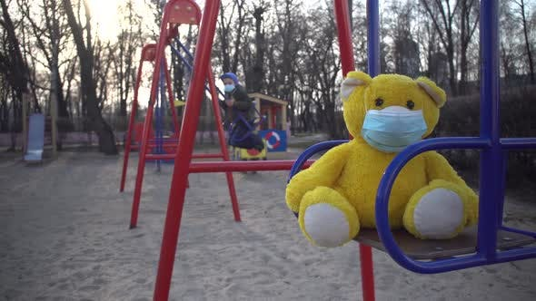 Thumbnail for Close-up of Yellow Teddy Bear in Face Mask on Children's Playground with Boy Riding on Swing