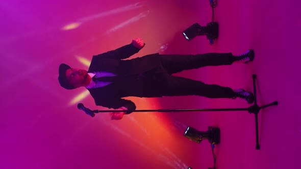 Vertical Video. Neon Lights and Strobe Lights a Man Sings in and Dances Into a Microphone. Funny