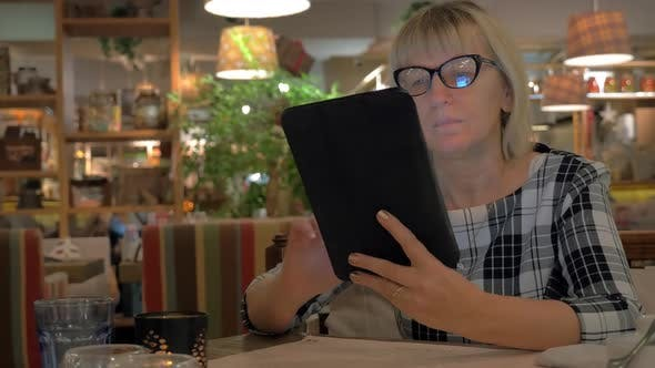Thumbnail for Senior Woman Browsing on Touch Pad in Cafe