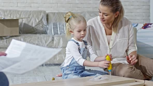 Thumbnail for Cute Girl Helping Parents to Build Furniture