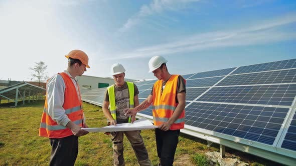 Technicians mounting solar panels. Workers installing alternative energy photovoltaic solar panels