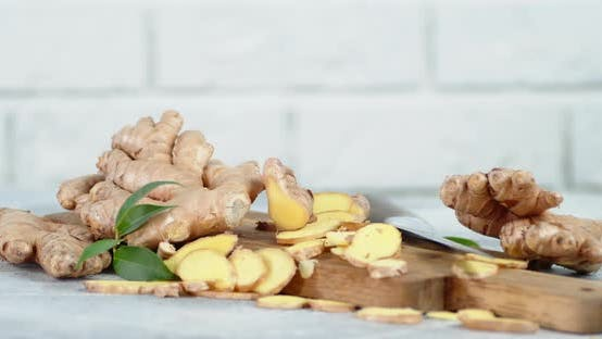Chopped Fresh Ginger on a Wooden Cutting Board Rotates Slowly