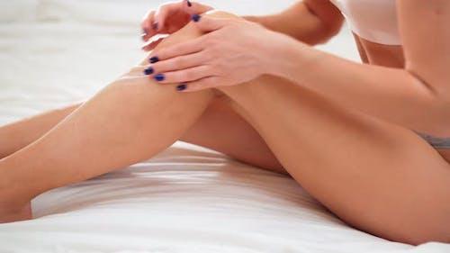 Moisturizer Cream on Her Slim Legs