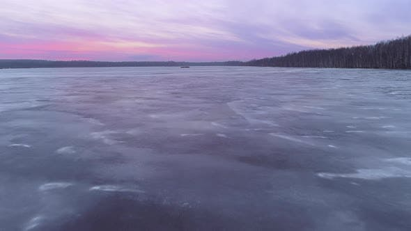 Flight Above the Frozen Lake at the Dusk with the Red Sunset on the Background
