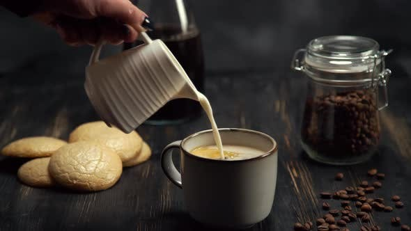 Slow Motion of Cream Being Poured Into a Cup of Coffee on Black Wood Table with Coffee Beans and