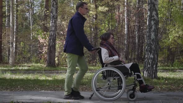 Thumbnail for Woman on wheelchair walking with boyfriend