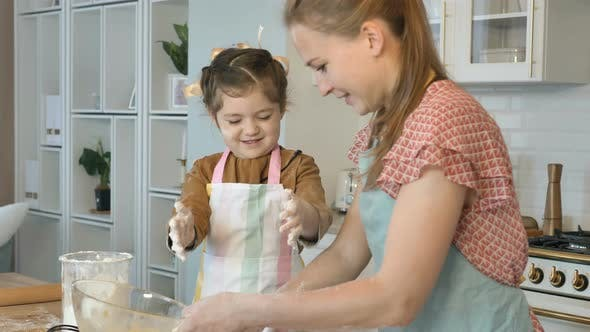Thumbnail for Happy Mother and Daughter Cook in the Kitchen, Daughter Laughs and Claps Her Hands and Flour Flies