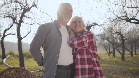 Thumbnail for Portrait of a Happy Senior Caucasian Couple Standing in Sunlight in the Foggy Park and Talking