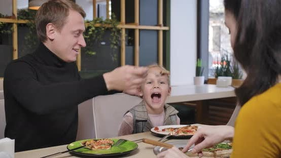 Happy Caucasian Father Feeding Daughter in Restaurant Playing Plane Spoon As Blurred Mother Eating