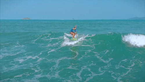 Surfer Flies on the Crest of a Wave, a Surfer Controls the Oar, Standing on a Surfboard. Surfer Is