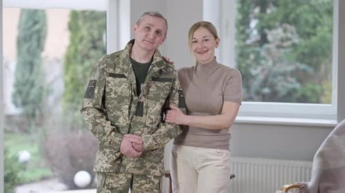 Portrait of Middle Aged Caucasian Military Man Posing with Woman Indoors at Home